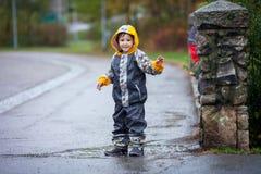 Garçon mignon en parc, jouant sous la pluie, sautant dans les magmas Image libre de droits