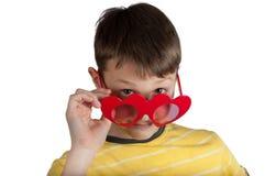 Garçon mignon en verres rouges de coeurs Photos stock