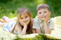 Garçon mignon et fille se trouvant sur la couverture Photographie stock libre de droits