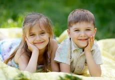 Garçon mignon et fille se trouvant sur la couverture Images libres de droits