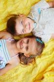 Garçon mignon et fille se trouvant sur la couverture Image stock