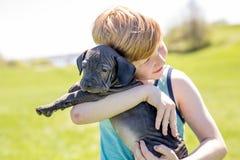 Garçon mignon et jeune dans le jardin tenant un chien de boxeur Photographie stock libre de droits