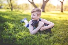 Garçon mignon et jeune dans le jardin tenant un chien de boxeur Images libres de droits