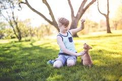 Garçon mignon et jeune dans le jardin tenant un chien de boxeur Images stock