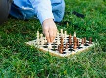 Garçon mignon et jeune dans les jeux bleus de chemise sur l'échiquier en bois sur l'herbe en parc Éducation, jeu intellectuel image libre de droits