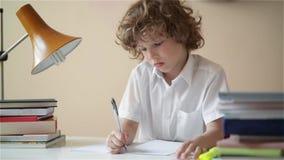 Garçon mignon faisant le travail L'éducation d'enfant, étudiant écrit dans un carnet clips vidéos
