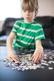Garçon mignon faisant un puzzle Photo stock