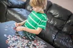 Garçon mignon faisant un puzzle Images stock