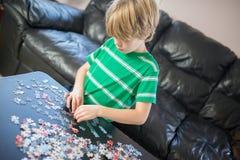 Garçon mignon faisant un puzzle Image stock