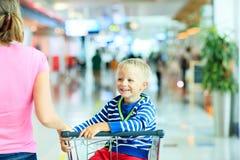 Garçon mignon heureux à l'équitation d'aéroport sur le chariot de bagage Image stock