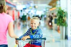 Garçon mignon heureux à l'équitation d'aéroport sur le chariot de bagage Photographie stock