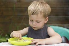 Garçon mignon heureux d'enfant de bébé mangeant du gruau lui-même avec la cuillère photos libres de droits