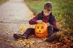Garçon mignon heureux de petit enfant avec le potiron de Halloween en parc d'automne photos libres de droits