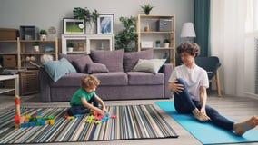 Garçon mignon jouant avec des jouets sur le plancher tandis que mère gaie faisant le yoga sur le tapis clips vidéos