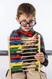 Garçon mignon jouant avec l'abaque contre le tableau blanc dans la salle de classe Images stock