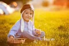 Garçon mignon, jouant avec l'avion sur le coucher du soleil en parc Image libre de droits