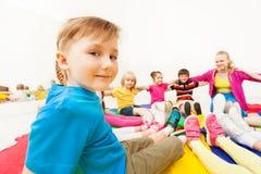 Garçon mignon jouant des jeux de cercle avec des amis dans le gymnase Photo stock