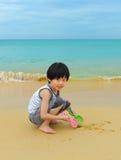 Garçon mignon jouant sur la plage Photos libres de droits