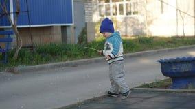 Garçon mignon marchant avec le bâton sur le trottoir photos libres de droits
