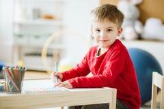 Garçon mignon portant la séance rouge de chandail à la petite table en bois photographie stock