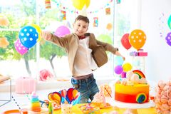 Garçon mignon près de table avec des festins à la fête d'anniversaire à l'intérieur image stock