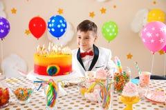 Garçon mignon près de table avec des festins à la fête d'anniversaire à l'intérieur image libre de droits