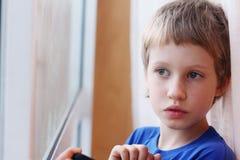 Garçon mignon regardant par la fenêtre Photos libres de droits