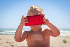 Garçon mignon riant tout en jouant avec le téléphone intelligent Photographie stock