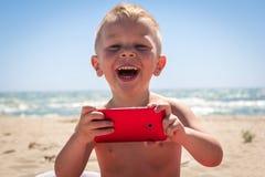 Garçon mignon riant tout en jouant avec le téléphone intelligent Photos stock