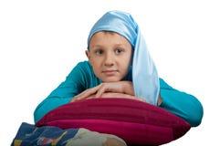 Garçon mignon s'étendant sur l'oreiller d'isolement Photo stock