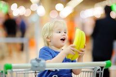 Garçon mignon s'asseyant dans le caddie et les bananes de participation dans un magasin de nourriture ou un supermarché photo stock