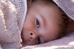 Garçon mignon se cachant sous l'essuie-main Image libre de droits