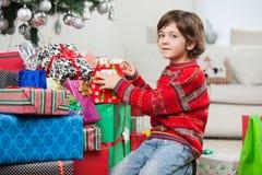 Garçon mignon se mettant à genoux par des cadeaux de Noël images libres de droits