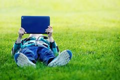 Garçon mignon se situant en parc et à l'aide du PC de comprimé Image libre de droits