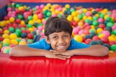 Garçon mignon souriant dans la piscine de boule photos libres de droits