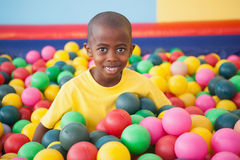 Garçon mignon souriant dans la piscine de boule image stock