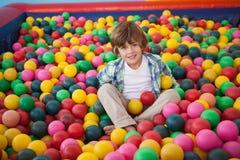 Garçon mignon souriant dans la piscine de boule image libre de droits