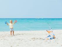 Garçon mignon sur la plage jouant avec un cerf-volant coloré Images stock