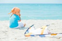 Garçon mignon sur la plage jouant avec un cerf-volant coloré Image stock
