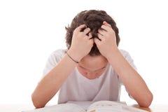 Garçon mignon sur le bureau étudiant et désespérant photos stock