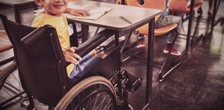 Garçon mignon sur le fauteuil roulant s'asseyant dans la classe image stock