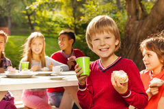 Garçon mignon tenant le petit gâteau avec son se reposer d'amis Image libre de droits