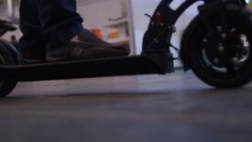 Garçon montant le scooter électrique de coup-de-pied, choisissant le transport de deux-roue sur l'exposition banque de vidéos
