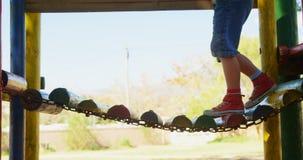 Garçon montant un petit pont accrochant en bois sur le terrain de jeu 4k banque de vidéos