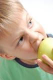 Garçon mordant une pomme photos libres de droits