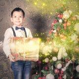 Garçon multiraceal heureux tenant un grand boîte-cadeau à Noël Photographie stock libre de droits