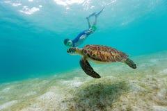 Garçon naviguant au schnorchel avec la tortue de mer photographie stock libre de droits