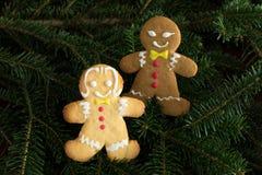Garçon noir de pain d'épice et fille blanche sur l'arbre de Noël Image stock