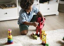 Garçon noir jouant le robot à la maison images stock