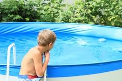 Garçon observant une piscine Images libres de droits